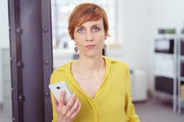 moderne frau im büro hält ein handy in der hand und schaut besorgt