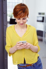 moderne geschäftsfrau steht im büro und schaut auf ihr mobiltelefon