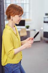 frau in einem modernen loft-büro liest die nachrichten am tablet