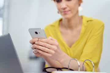 frau sitzt am schreibtisch und liest eine nachricht auf dem smartphone