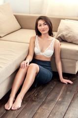 Asian girl in skirt sitting on floor