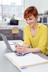 moderne geschäftsfrau sitzt am tisch und schaut auf ihr mobiltelefon