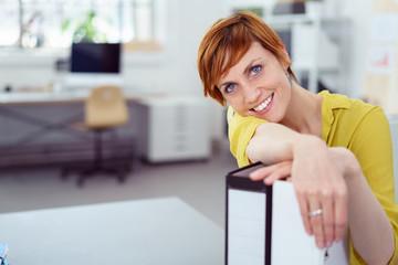lächelnde mitarbeiterin im büro stützt ihren kopf auf aktenordner