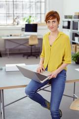 moderne geschäftsfrau sitzt mit laptop auf dem schreibtisch im büro