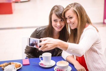 Women taking a selfie on phone while having coffee in mall