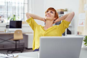 zufriedene junge frau im büro lehnt sich entspannt zurück