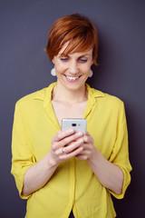 frau schaut lächelnd auf ihr smartphone