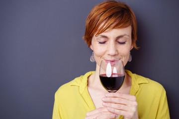 frau mit kurzen, roten haaren riecht an einem glas rotwein