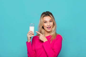 Blonde young woman a glass of milk on blue