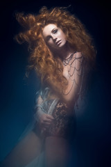Beautiful fashionable red-haired girl in  transparent dress,  mermaid image with creative hairstyle curls. Fashion beauty style.