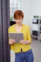 frau steht im büro und liest nachrichten am tablet-pc