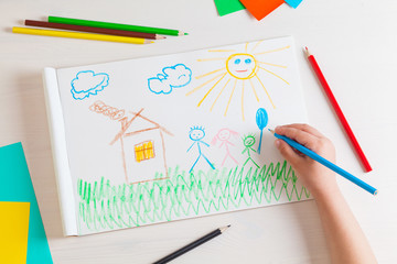 Child draws a pencil drawing of the house and his family.