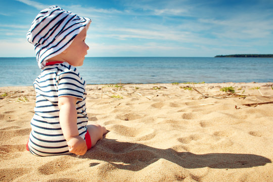 Little baby boy sitting on the beach in summer day