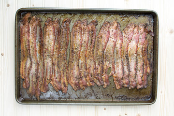 Baked Peppercorn Bacon in in baking pan on wood background