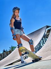 Teen girl rides his skateboard in skatepark outdoor. Skateboarding is extreme sport.