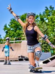 Teen girl rides his skateboard outdoor. Teen girl rides his skateboard outdoor. Child girl wearing  roller Skates on background.