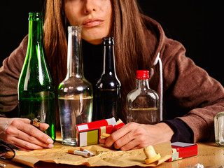 Girl in depression drinking alcohol and smokes cigarettes in solitude. Drinking habits. Girl is heavy drinkers.