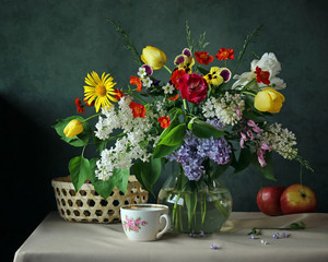 Still life with spring flowers in a glass jug.