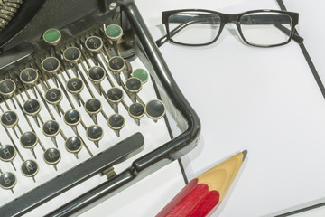 antique typewriter with blank book and reading glasses