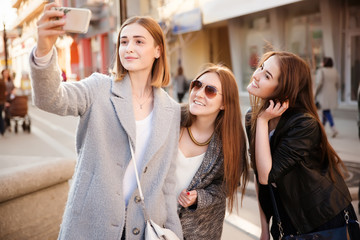 Lifestyle sunny image of best friend girls taking selfie on smartphone
