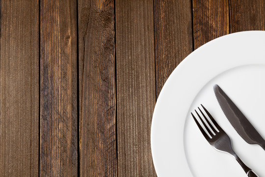 Fork and knife with white plate on dark wooden background, empty space on left