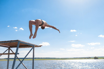 Young man jumping from tower into the water