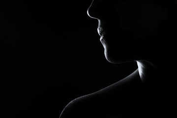 Silhouette of a woman face in black and white rim lighting