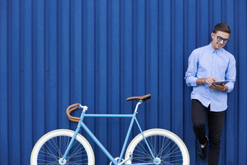 Modern man with tablet and bike