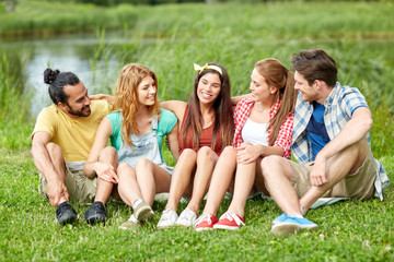 group of smiling friends talking outdoors