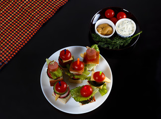 Small snacks canape with cherry tomatoes, cheeze, sausages and vegetables on bread on skewers on white plate with plate of sauces