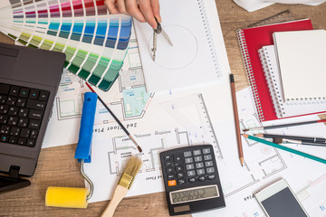 Professional worker drawing on house project with work tools