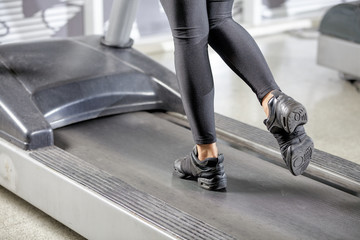 Woman running in a gym on a treadmill concept for exercising