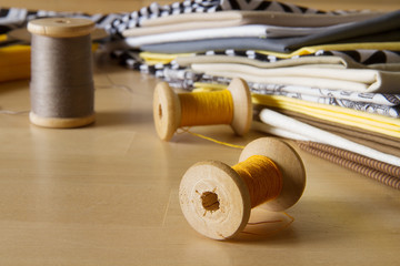 Modern patchwork fabrics in black, brown, white, yellow and grey on the wood table with yellow sewing spool