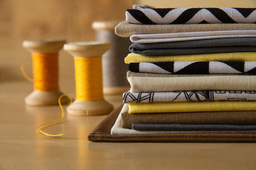 Modern patchwork fabrics in black, brown, white, yellow and grey on the wood table with yellow sewing spools
