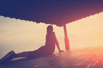 Fotomurais - Silhouette of woman in yoga position, sun shelter near ocean. Intentional sun glare and vintage color