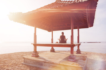 Fotomurais - Young woman doing yoga practice on the beach. Blurred effect, lens flare effect, intentional sun glare