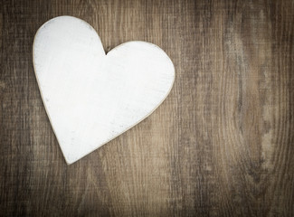 Wooden heart on brown wood plank background