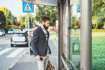 youn handsome bearded man at bus stop
