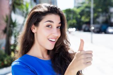 Optimistische Frau im blauen Shirt zeigt Daumen
