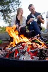 Flames in fire pit, couple in background
