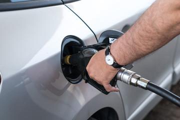 Mano di uomo che inserisce la pistola erogatrice di carburante nel serbatoio dell'autovettura per il rifornimento