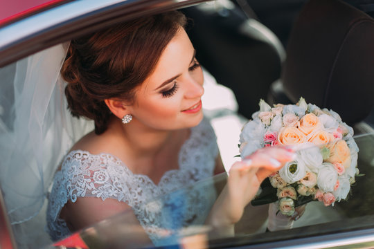 Gorgeous bride with beautiful smile is sitting in wedding car and holding summer flowers bouquet