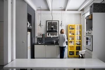 Rear view of woman preparing food at kitchen hob