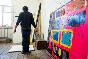Rear view of male artist standing in front of blank canvas