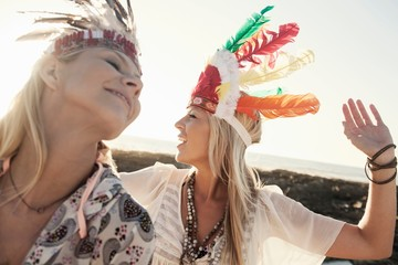 Young women wearing feather headdresses looking away smiling