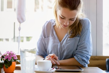 Young woman in cafe writing, looking at camera smiling