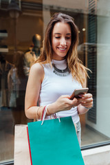 Woman using mobile phone after shopping