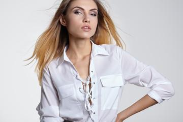 Glamorous beautiful blonde woman in a stylish white top  posing