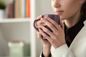 Close up of young beautiful woman hands holding hot cup of coffe