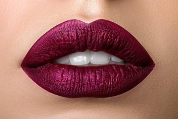 Close up view of beautiful woman lips with purple matt lipstick